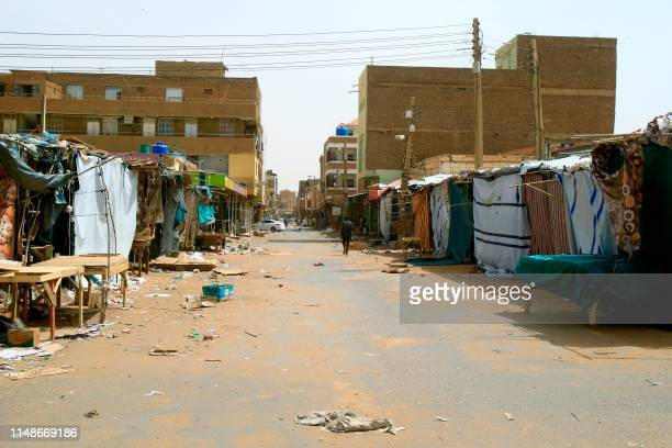 A Sudanese man walks past closed shops and makeshift stalls at the Omdurman market in Khartoum's twin city on June 9 2019 Sudanese police fired tear...