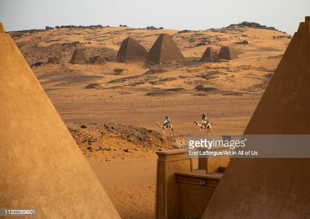 Sudanese men and their camels in front of the pyramids of the kushite rulers at Meroe Northern State Meroe Sudan on December 28 2018 in Meroe Sudan