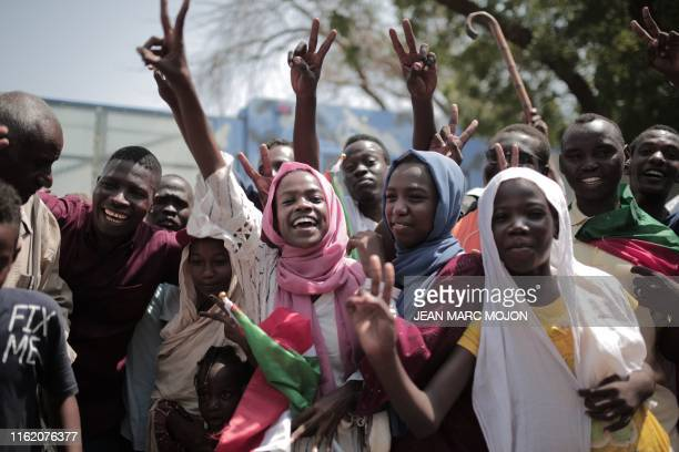 Sudanese men and women celebrate outside the Friendship Hall in the capital Khartoum where generals and protest leaders signed a historic...
