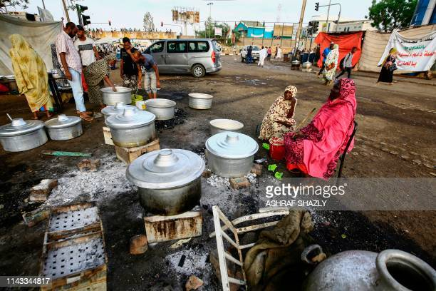TOPSHOT Sudanese men and women prepare food for the demonstrators just before the time for breaking the fast during the holy month of Ramadan as...