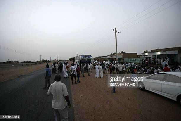 Sudanese men arrive by bus to break the fast with a dinner by the side of the Khartoum highway in the village of alNuba on June 23 2016 during the...