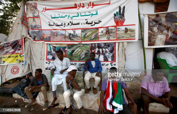 Sudanese men displaced from Darfur sit next to a tent outside the military headquarters in the capital Khartoum on May 22 2019 Thousands of Sudanese...
