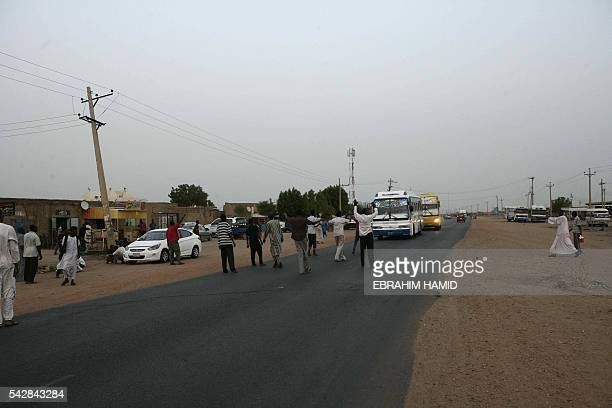 Sudanese men men halt a bus ahead of breaking the fast with a dinner by the side of the Khartoum highway in the village of alNuba on June 23 2016...