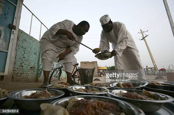 Sudanese men prepare food before an Iftar dinner by the side of the Khartoum highway in the village of alNuba on June 23 2016 during the Muslim...