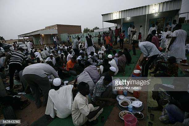 Sudanese men prepare to break the fast with a dinner by the side of the Khartoum highway in the village of alNuba on June 23 2016 during the Muslim...