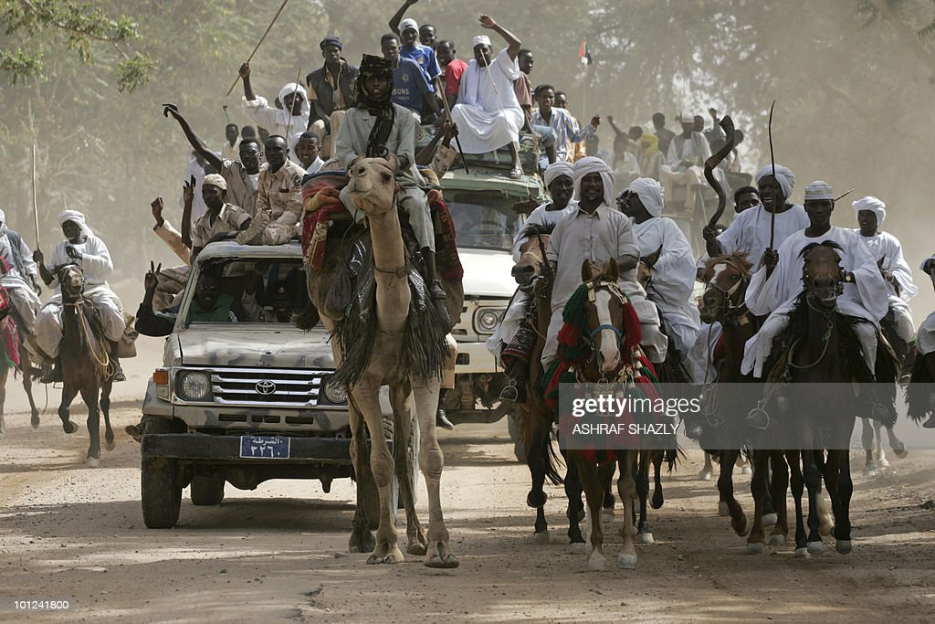 Sudanese men ride their horses, camels and cars during a ceremony for the visit of President Omar al-Beshir in the city of Zalingei, West Darfur on April 7, 2009. The International Criminal Court (ICC) issued an arrest warrant on March 4 for Beshir for alleged war crimes including genocide in Darfur.