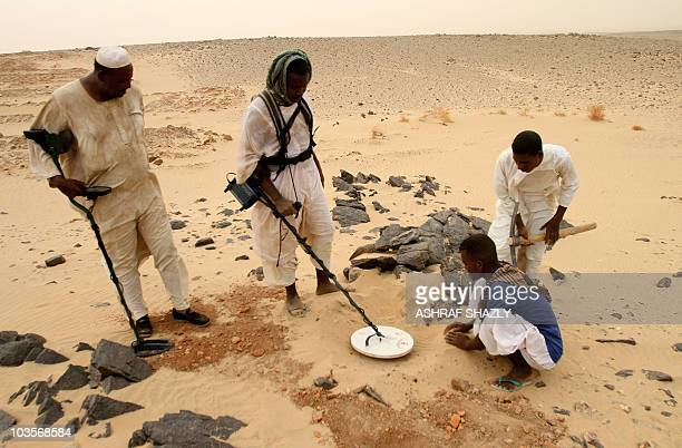 Sudanese men search for gold with metal detectors in the desert near the village of alShirik in northern Sudan on August 8 2010 Rising gold prices...