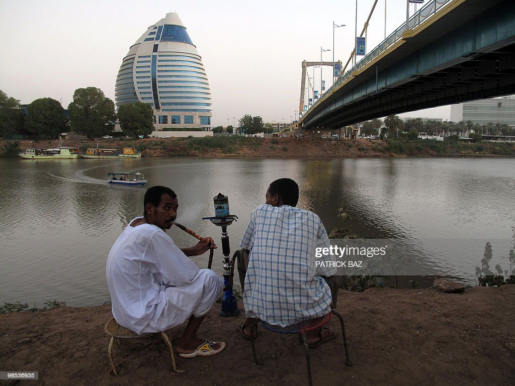 Sudanese men smoke waterpipe by the Nile under a bridge leading to the Burj al-Fateh hotel (back) in Khartoum on April 18, 2010. Criticism of Sudan's multi-party elections by foreign observers including former US president Jimmy Carter has encouraged the opposition, but also damages the credibility of the former rebels ruling the south, where an independence referendum is due next year.