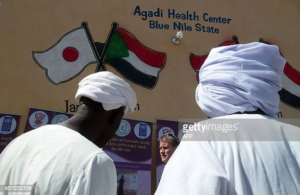 Sudanese men stand in front of the Agadi Health Centre as a Norwegian diplomat Jon Anton Johnson passes in front of them in the Sudanese area of...