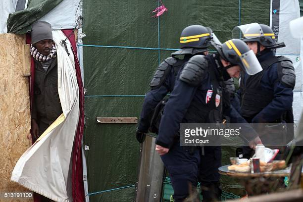Sudanese migrant looks out from his hut as police officers prepare to clear part of the 'jungle' migrant camp on March 01 2016 in Calais France...