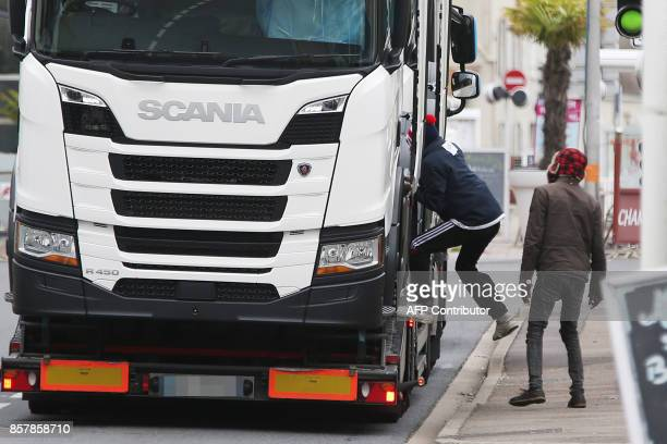 Sudanese migrants jump in a truck in Ouistreham near Caen northwestern France on October 5 2017 A ferry boat passes from Ouistreham to Portsmouth...
