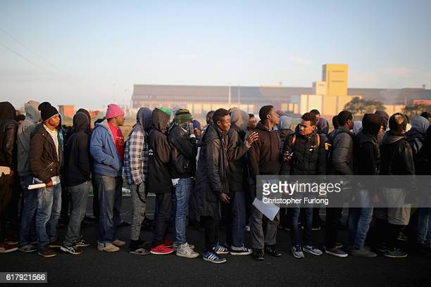 Sudanese migrants queue in the cold weather to board buses and leave the notorious 'Jungle' camp before authorities demolish the site on October 25...