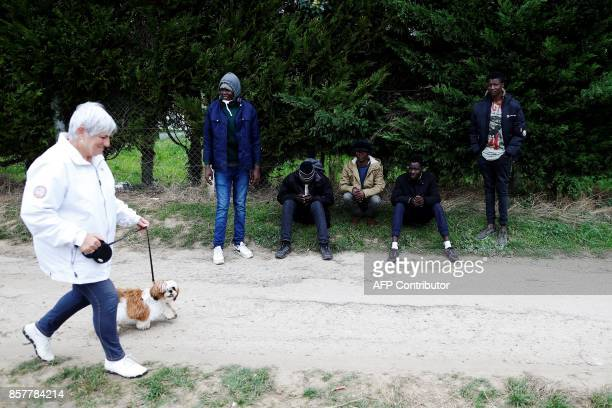 Sudanese migrants wait on the side of a road as a woman with a dog walks past in Ouistreham near Caen northwestern France on October 5 2017 Migration...