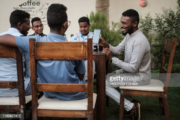 Sudanese Mohamed Omar sits near his friends at a cafe in which an hour of internet costs 50 Sudanese pounds which is approximately one US dollar on...