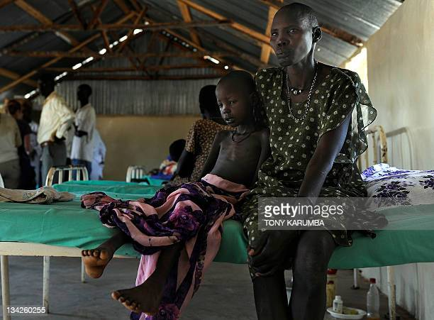 Sudanese mother cradles her emaciated daughter ailing from malaria and anaemia at a German aid agency Sign of Hope run clinic in Nyal in South Sudan...