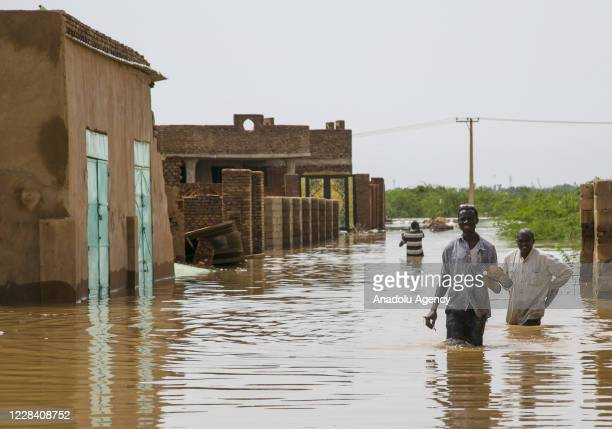 Sudanese people wade through the floodwaters at Umm Dawm district in Khartoum, Sudan on September 8, 2020.