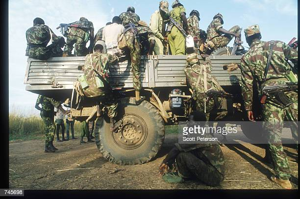 Sudanese People's Liberation Army soldiers climb aboard a truck November 13, 1993 in southern Sudan. SPLA members were offered amnesty in exchange...