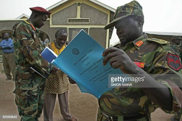 Sudanese People's Liberation Army soldiers look at a copy of the comprehensive peace agreement 23 January 2005 before their meeting in Rumbek The...