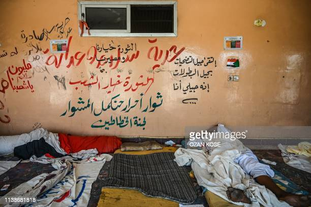 Sudanese placard maker sleeps outside a building during a protest outside the army headquarters in the capital Khartoum on April 22, 2019. - Sudan's...