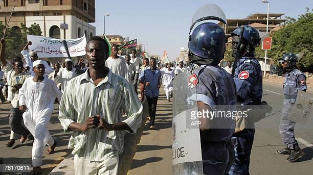 Sudanese policemen stand guard as demonstrators march with sticks and banners during a protest in Khartoum against the verdict handed down to a...