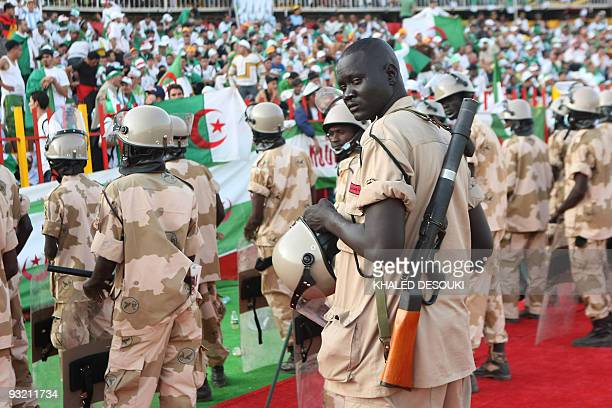 Sudanese policemen stand guard in front of Algerian fans ahead of the 2010 World Cup qualification playoff between Egypt and Algeria in Khartoum on...