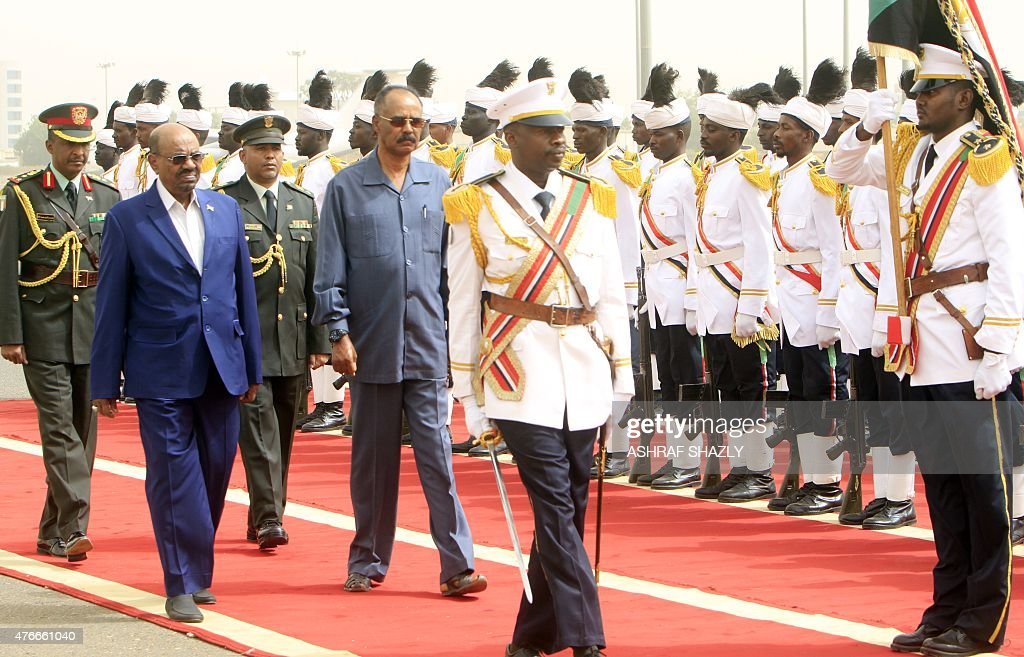Sudanese President Omar al-Bashir (L) and Eritrean President Isaias Afwerki (R) review the honor guard during the latter's welcome ceremony in the capital Khartoum, on June 11, 2015.