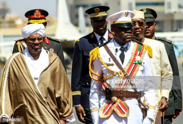 Sudanese President Omar alBashir and his Chadian counterpart Idriss Deby inspect an honour guard upon arrival at Khartoum International Airport...