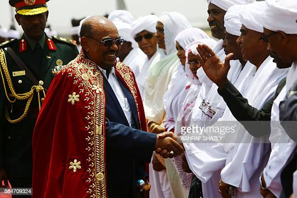 Sudanese President Omar alBashir greets officials upon his arrival at the airport on July 30 2016 in the capital Khartoum Omar alBashir was honoured...