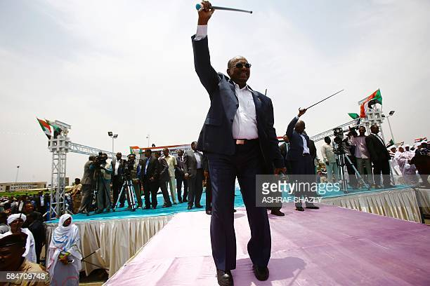 Sudanese President Omar alBashir greets the audience during a ceremony in his honour upon his return in the country from Ethiopa on July 30 2016 in...