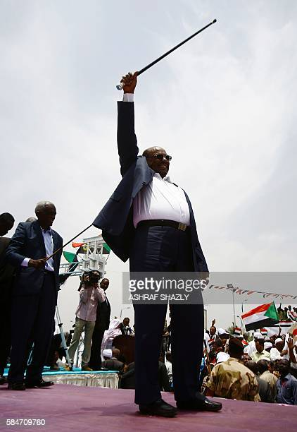 Sudanese President Omar alBashir greets the audience during a ceremony in his honour upon his return in the country from Ethiopia on July 30 2016 in...