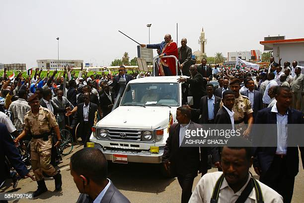 Sudanese President Omar alBashir greets the audience from his car as he arrives for a ceremony in his honour upon his return in the country from...