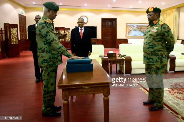 Sudanese President Omar alBashir watches as Defence Minister General Awad Ibnouf is sworn in as the first vice president at the Presidential palace...