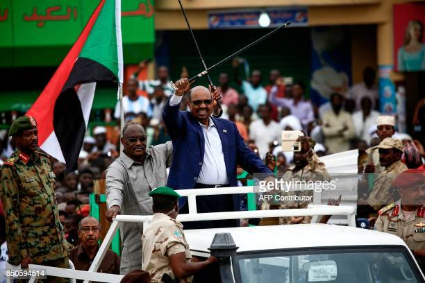 Sudanese President Omar alBashir waves a walking stick as he rides in the back of a pickup truck in an advancing motorcade in Nyala the capital of...