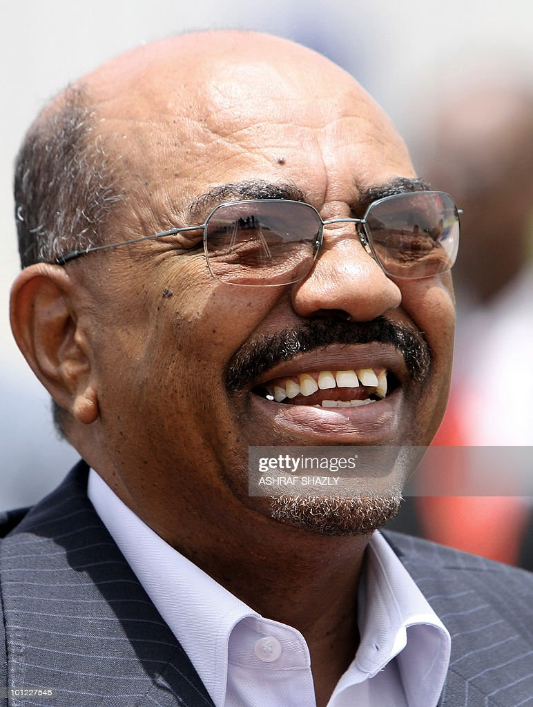 Sudanese President Omar al-Beshir smiles as he waits for his Eritrean counterpart Isaias Afwerki at Khartoum airport on May 26, 2010. Beshir is to be sworn in for a new term on May 27, ahead of a vote on southern independence and with an international war-crimes indictment hanging over him.