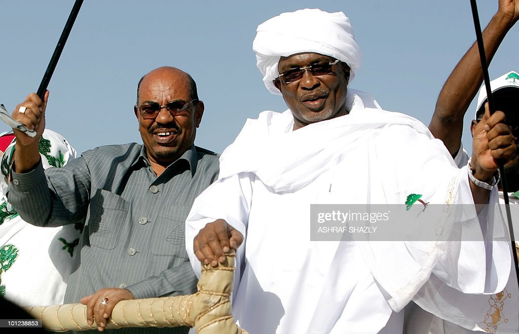 Sudanese President Omar al-Beshir (L) waves his trademark cane as he rides at the back of vehicle with governor Yussef Keber (R) during a rally in El-Fasher, the capital of North Darfur state, on February 24, 2010. 'The war in Darfur is over,' Beshir said in a speech in the war-torn region, adding that 57 members of a key rebel group, 50 on death row, had been freed.