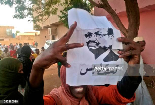 A Sudanese protester carries a portrait of President Omar alBashir with Arabic writing that reads down and that is all during an antigovernment...
