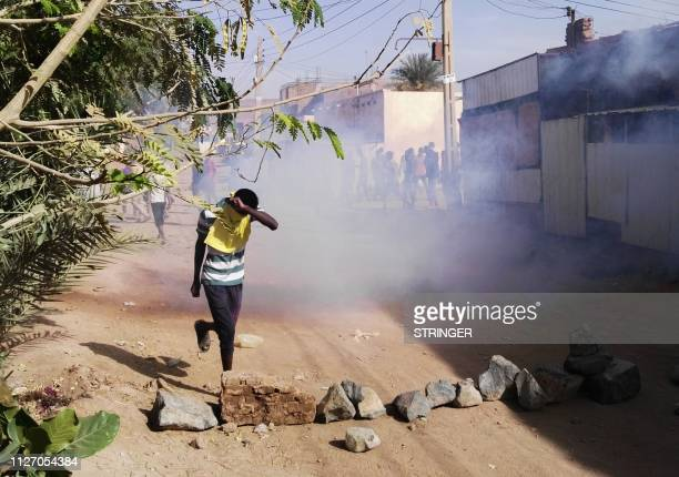 A Sudanese protester covers his face from tear gas during an antigovernment demonstration in the Sudanese capital Khartoum's district of Burri on...