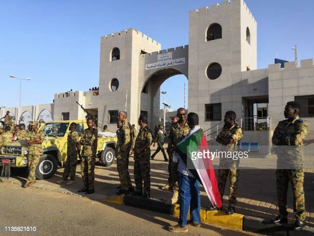 A Sudanese protester draped in the national flag speaks with a soldier as they rally for a second day outside the military headquarters in the...