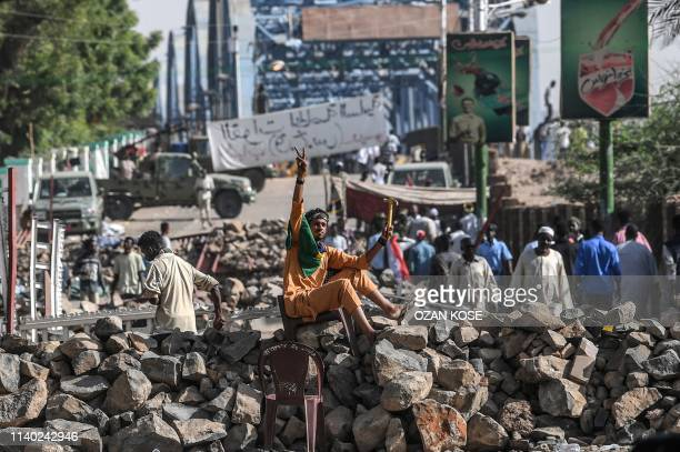 A Sudanese protester flashes the V for victory sign as he sits atop a makeshift barricade during a sitin outside the army headquarters in the capital...