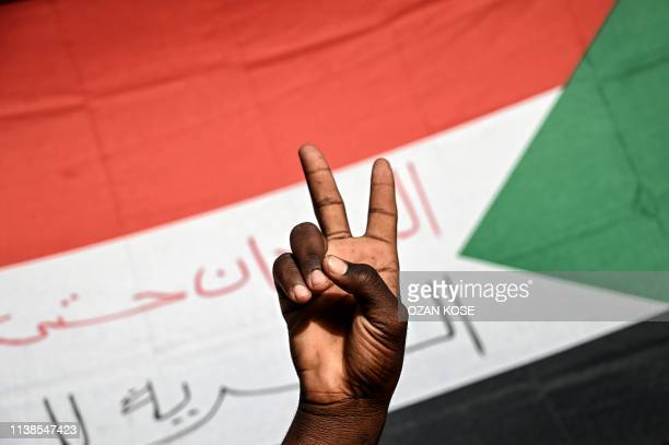 Sudanese protester flashes victory sign in front of a national flag during a protest outside the army headquarters in the capital Khartoum on April...
