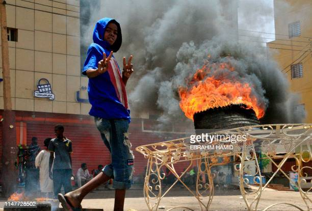 A Sudanese protester gestures as he walks past a burning tyre near Khartoum's army headquarters on June 3 2019 after security forces broke up a...