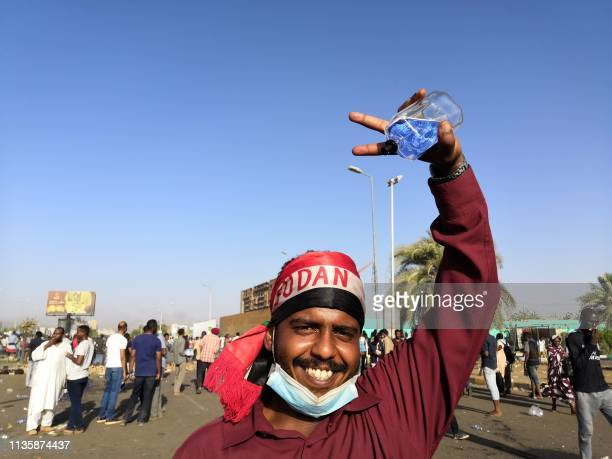 A Sudanese protester gestures during a rally in front of the military headquarters in the capital Khartoum on April 9 2019 Thousands of Sudanese...