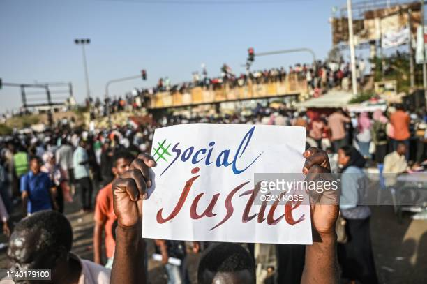 Sudanese protester raiser a placard during a sitin outside the army headquarters in the capital Khartoum on April 29 2019 Sudan's army rulers and...