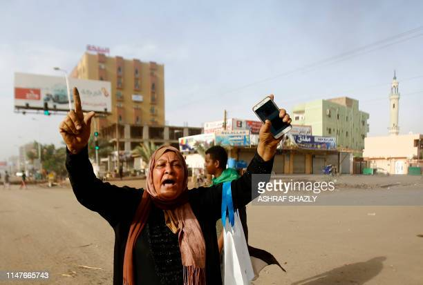 Sudanese protester reacts as military forces tried to disperse a sit-in outside Khartoum's army headquarters on June 3, 2019. - At least two people...