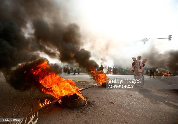 Sudanese protester walks past burning tyres as military forces tried to disperse a sit-in outside Khartoum's army headquarters on June 3, 2019. - At...
