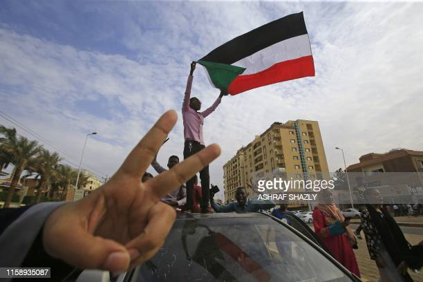 A Sudanese protester waves a national flag as another flashes the V for victory gesture as they take part in a demonstration called for by the...