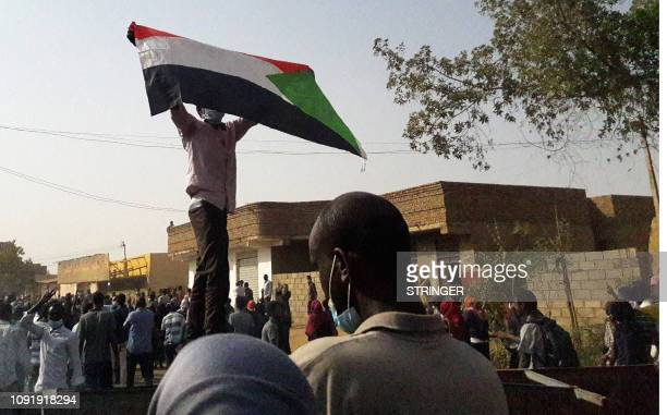 A Sudanese protester waves a national flag during an antigovernment demonstration in the capital Khartoum's twin city of Omdurman on January 31 2019...