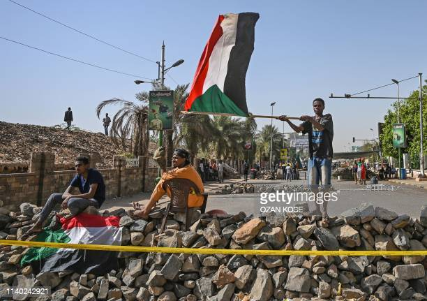 A Sudanese protester waves a national flag near a makeshift barricade during a sitin outside the army headquarters in the capital Khartoum on April...