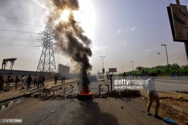 Sudanese protesters burn tyres and barricade the road in Khartoum's twin city of Omdurman on June 3, 2019. - At least five protesters were shot dead...
