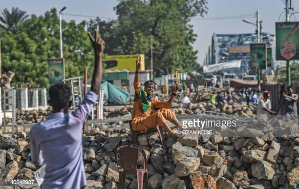 TOPSHOT Sudanese protesters flash the V for victory sign as they man a makeshif barricade during a sitin outside the army headquarters in the capital...